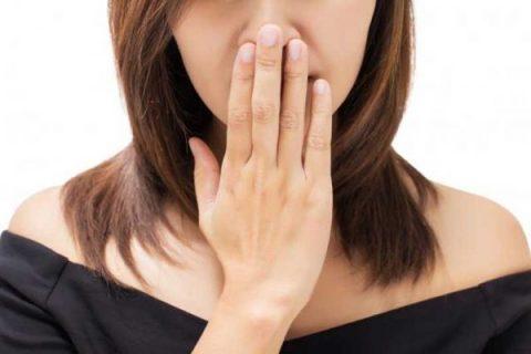 Mal aliento - Mujer tapándose la boca