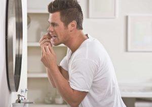 manchas en los dientes - hombre usando hilo dental